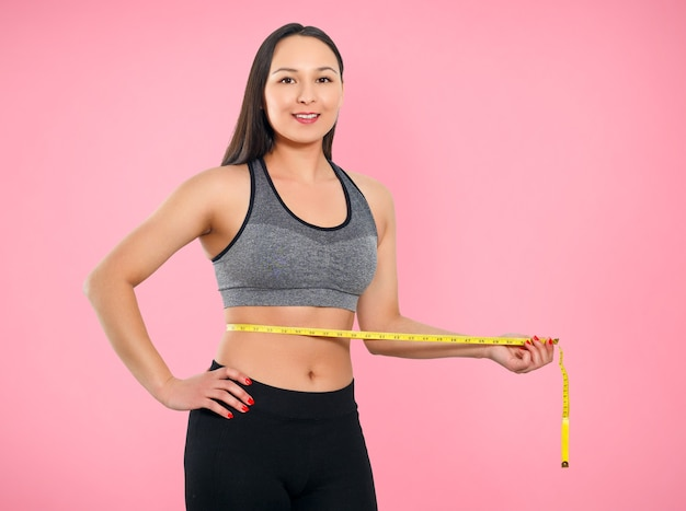 A slender woman measures her waist with a measuring tape on pink background. Premium Photo