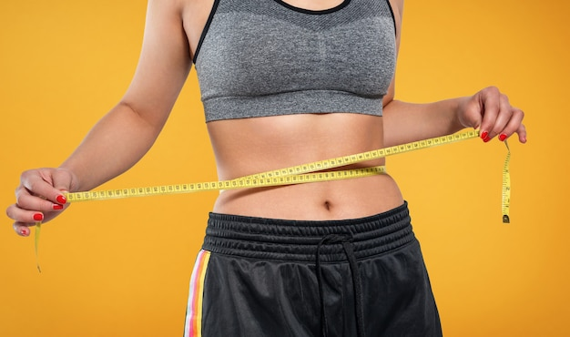 A slender woman measures her waist with a measuring tape on a yellow background.