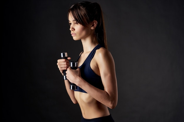 Slender woman muscle workout slim figure exercise gym dark background. high quality photo