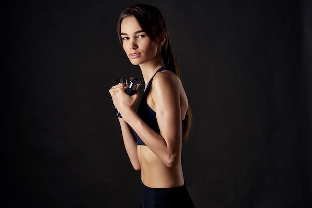 ほっそりした女性の筋肉のトレーニングスリムな体型エクササイズジム暗い背景