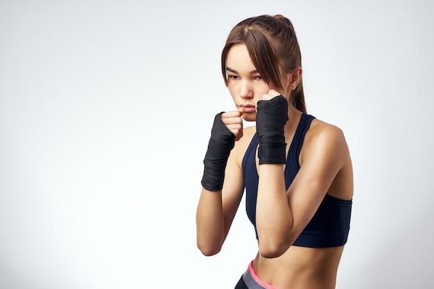ほっそりした女性の筋肉のトレーニングスリムな体型運動ジム明るい背景