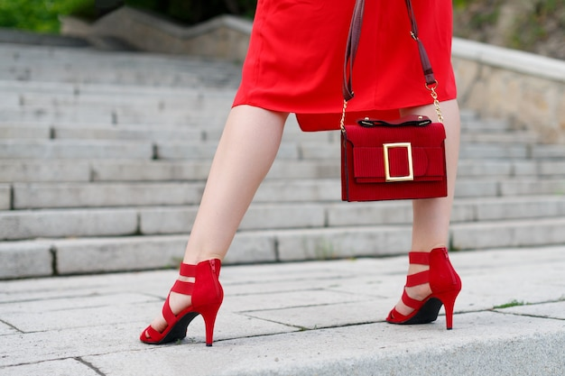 A slender woman in a red dress with a handbag climbs elegantly up the stairs, rear view.