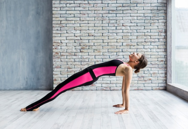 Slender woman standing in an upward plank