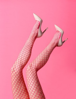 Slender woman wearing sexy pink fishnet stockings and stilettos posing with feet up