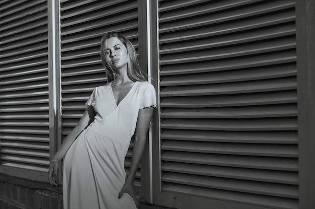ほっそりした女性は、金属製のシャッターの近くの通りでポーズをとるファッショナブルなドレスを着ています。スペースをコピーします。モノクロカラー