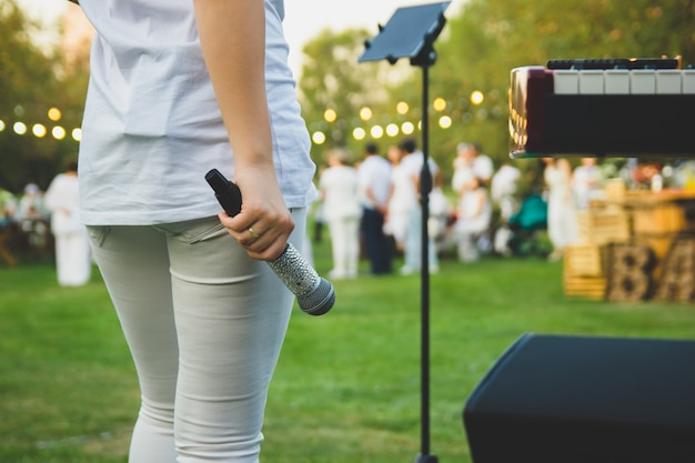 A slender woman in white clothes with a microphone in her hand stands on the background of people.