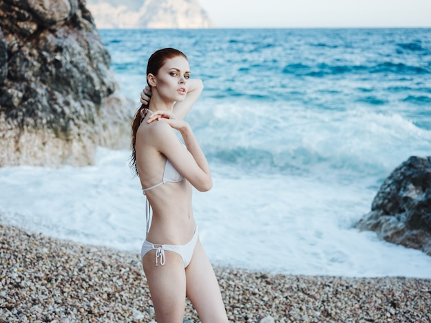 A slender woman in a white swimsuit near the ocean and white foam splash in waves. high quality photo