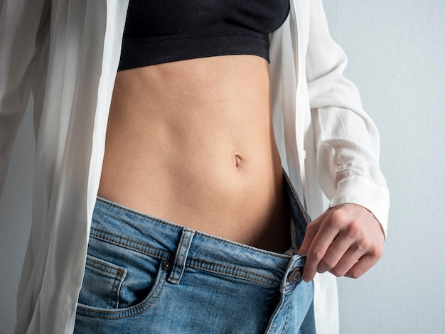 A slender woman with a bare stomach shows how she lost weight, holding her jeans with her hand. the concept of diet, weight loss, healthy lifestyle