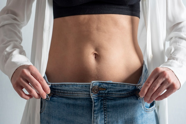 A slender woman with a bare stomach shows how she lost weight. jeans have become too big. the concept of diet and healthy eating Premium Photo