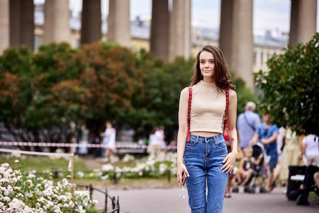 Стройная женщина лет стоит на открытом воздухе возле фонтана