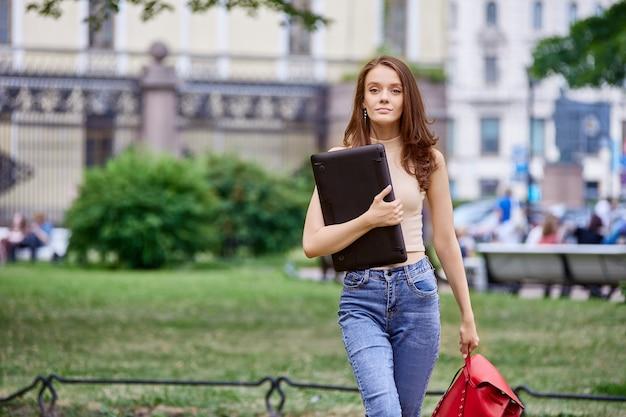 Стройная студентка пришла в парк с ноутбуком