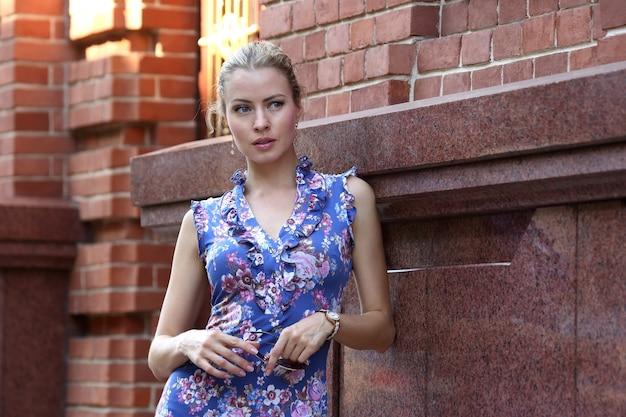 건물의 벽 근처에 서있는 날씬한 젊은 아름다운 여자