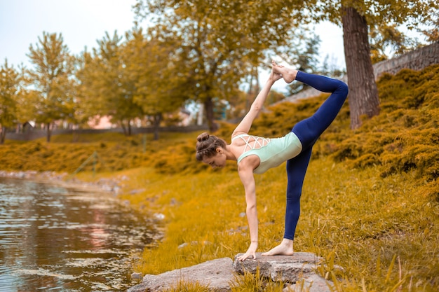 Slender young brunette yogi performs challenging yoga exercises  green grass in autumn against the  of nature. beautiful sporty girl standing in half moon pose