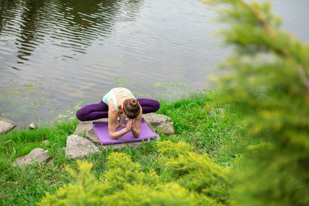 Slender young brunette yogi performs challenging yoga exercises on the green grass in the summer against the backdrop of nature