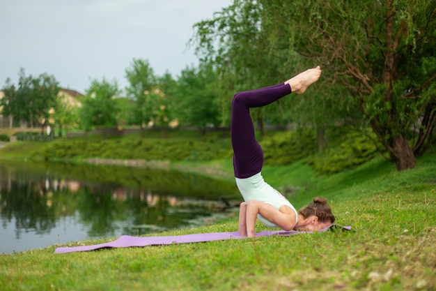 Slender young brunette yogi performs challenging yoga exercises on the green grass in the summer