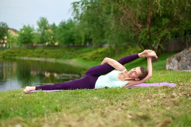 날씬한 젊은 갈색 머리 요기는 여름에 푸른 잔디에서 도전적인 요가 운동을 수행합니다.
