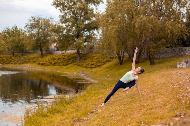 Slender young brunette yogi performs challenging yoga exercises on the yellow grass in autumn against the of nature