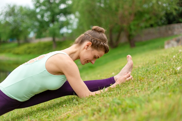 Slender young brunette yogi performs complex yoga exercise on green grass in the summer