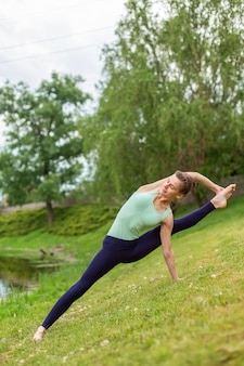 Slender young brunette yogi performs complex yoga exercise on green grass in summer