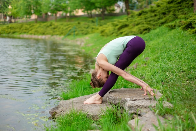 Slender young brunette yogi performs complex yoga exercise on green grass