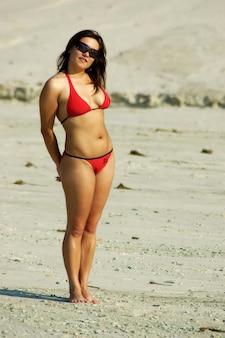 Стройная молодая кавказская женщина в солнечных очках и розовом купальнике загорает на солнце на пляже в солнечный жаркий летний день на море. концепция отдыха и релаксации