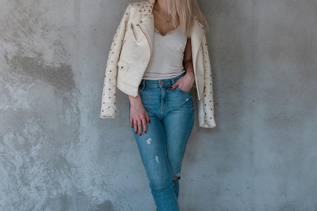 Стройная молодая европейка в модной весенней кожаной куртке в белой футболке и рваных синих джинсах стоит у серой бетонной стены