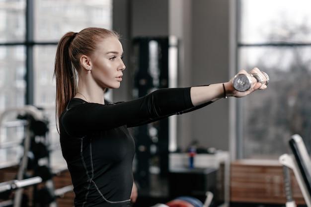 黒のスポーツウェアに身を包んだほっそりした少女は、たくさんのスポーツ用品を備えたモダンなジムでダンベルを使ってエクササイズをしています。