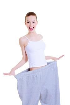 Стройная молодая красивая девушка на больших брюках после диеты
