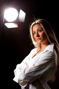 검은 배경에 스튜디오에서 포즈 흰 셔츠에 날씬한 젊은 꽤 긴 머리 소녀 모델. 매력과 젊음의 개념. 광고 공간
