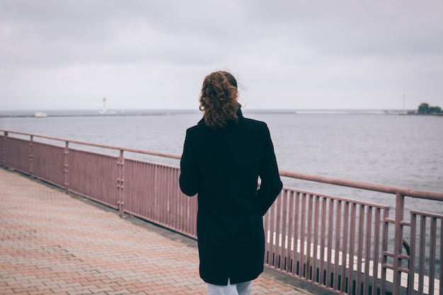 Slender young woman in a black coat walks