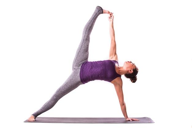 ヨガの練習をしているほっそりした若い女性。白い背景の上に分離。