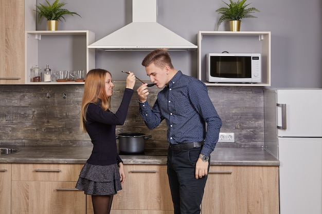 ほっそりした若い女性は、白人男性に台所に立っている間に調理する料理の味を与えます。