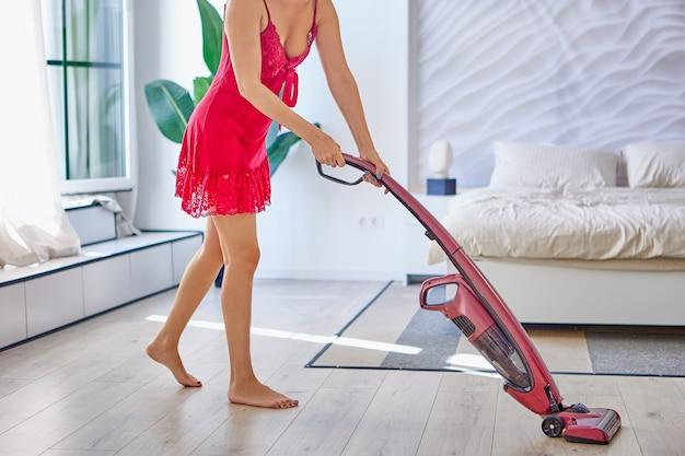 분홍색 잠옷을 입은 날씬한 젊은 여성이 무선 진공 청소기로 방을 청소합니다