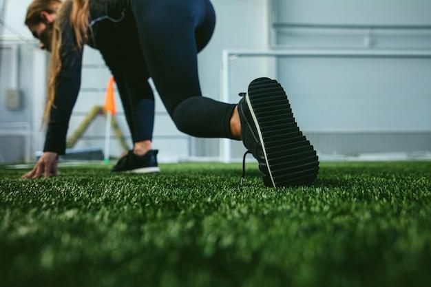 スポーツウェアの細い若い女性は、足のスポーツスタジアムのクローズアップに従事しています