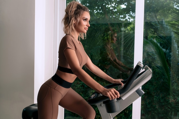 A slender young woman is training on an exercise bike in a gym in fashionable sportswear. side view