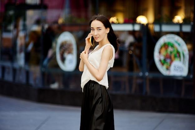 야외에서 휴대 전화로 날씬한 젊은 여자 회담