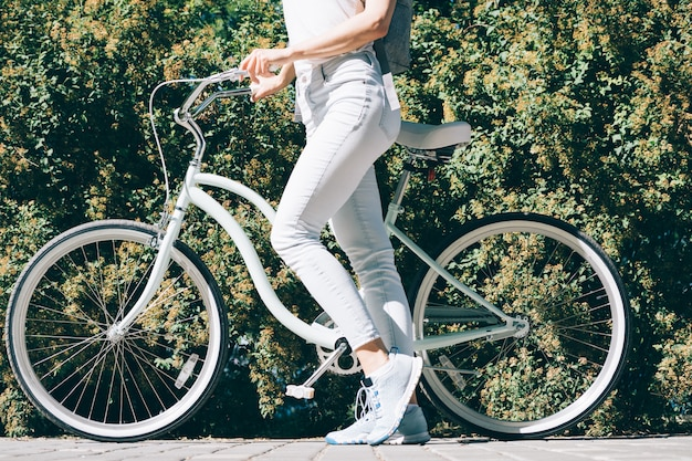 Slender young woman in a white t-shirt and jeans stands in front of her stylish bike