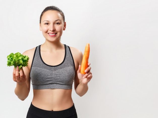 Slender young woman with a beautiful figure holds vegetables in her hands