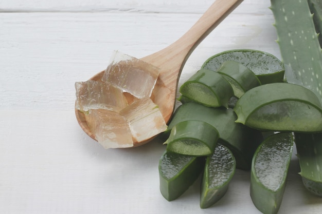 Slice aloe vera is in a wooden spoon placed on a white wooden.
