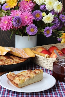 Slice of apple pie on a plate and autumn bouquet of chrysanthemums and asters