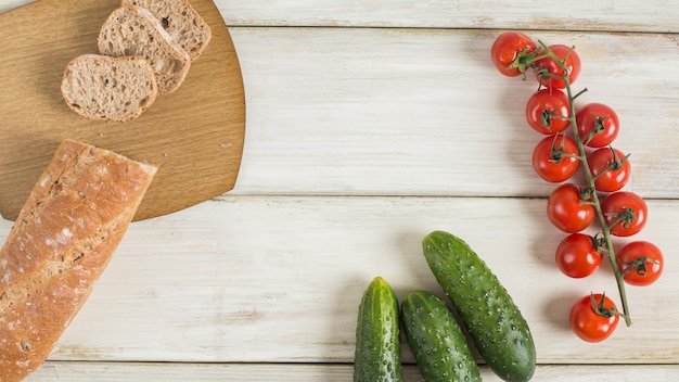 Slice of baguette; cucumber and cherry tomatoes on wooden desk
