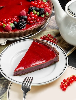 Slice of berry cheesecake served next to cheesecake and teapot