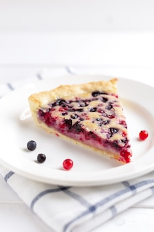 Slice of blueberry and red currant pie on rustic wooden table