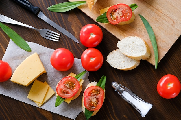 Slice of bread, sandwiches, tomatoes, salt shaker, cheese