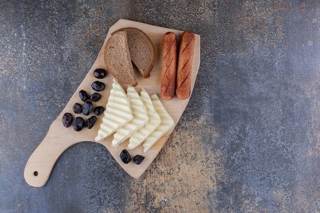 Una fetta di pane servita con salsicce e formaggio su una tavola di legno