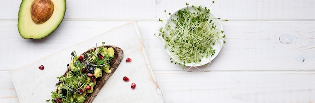 Slice of bread with avocado pasta and pomegranate concept