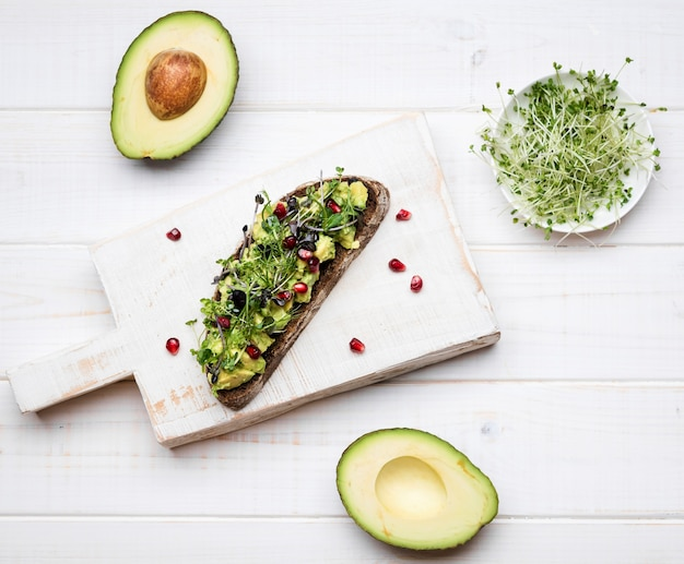 Slice of bread with avocado pasta and pomegranate on wooden board