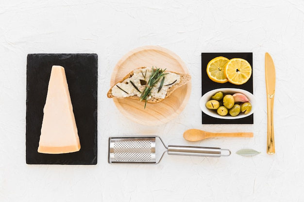 Slice of bread with cheese, rosemary, olives and lemons slice on white backdrop