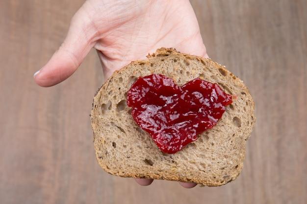 Slice of bread with fruit jam heart shape