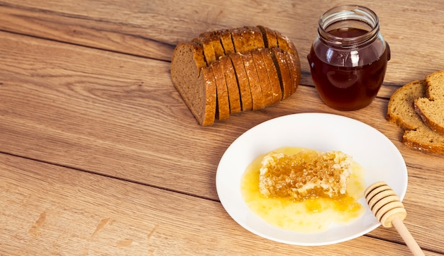 Slice of bread with honey and honeycomb on wooden texture backdrop